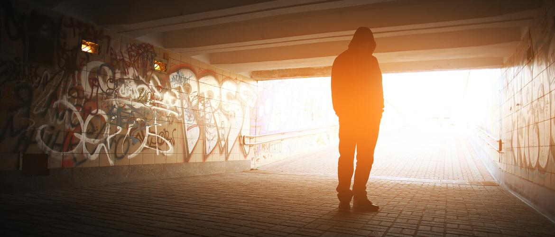 Depressed person stands under a bridge.